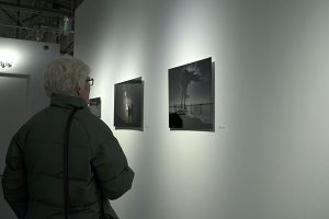 Women looking at photography that is printed on aluminum, which is hanging on the wall